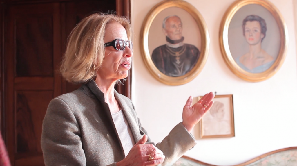 The Countess, Carolina Levetzow Lantieri, explaining the history of her family. In the background, the portraits of the Baron, Charles Levetzow Lantieri, and the Countess, Dorothea Saurma-Hoym.