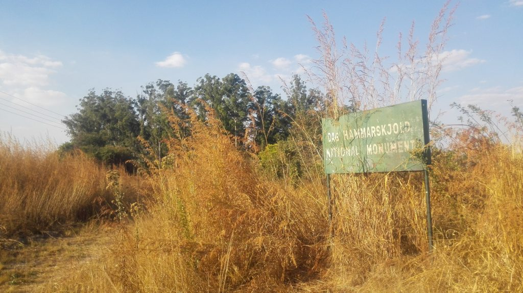 In the Picture is a billboard with words saying 'Dag Hammarskjold National Monument'