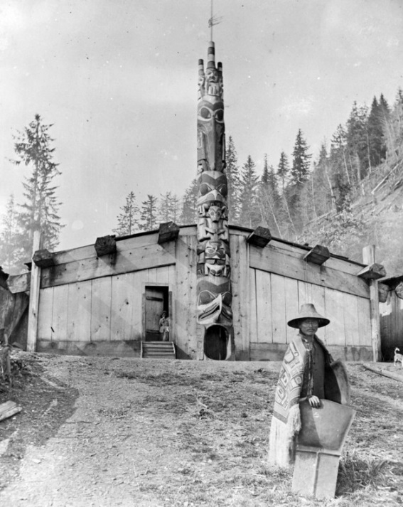 Hadia chief in his ceremonial garments- a spruce-root crest hat and Chilkat robe, holding copper shields.