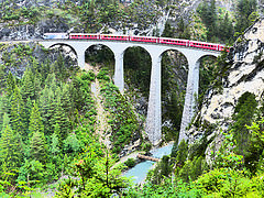 """I visited this WHS in June 2014. After spending quite a lot of money to visit other Swiss WHS and mostly because on the day it wasn't sunny, I decided to visit the main train stations and scenic points of the Albula and Bernina passes by car. Considering the many tunnels involved, I think that this approach let me see much more than what I would have seen on the train and I could read the different information boards and take photos at leisure instead of seeing the sites for some split seconds on the Bernina Express. The main railway sights are Rothenbrunnen, the Solisviaduct, Pontresina, Morteratsch, Lago Bianco in Ospizio Bernina, Valposchiavo, the """"round viaduct"""" of Brusio and the Landwasserviaduct. The latter was definitely my favourite and the true highlight of my road trip through mountain passes. From the Filisur train station, there's a short hike to a panoramic point over the Landwasserviaduct and a longer hike beneath it with a number of information boards along both ways. In the future I might be tempted to take the Glacier Express instead of the Bernina Express which costs around 100 euros for the return trip from Chur to Tirano."""