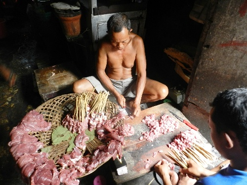 A worker cutting goat meat to prepare Bustaman Goat Gulai