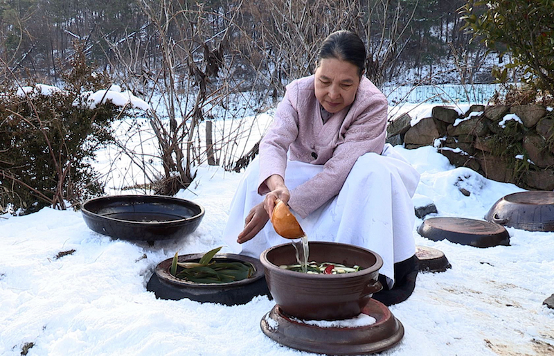 A grandmother opens a Kimchi pot. Photo credit: Cultural Heritage Administration, Republic of Korea