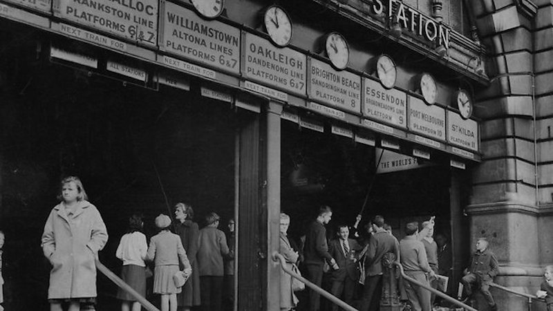 People wait under the clocks at Flinders Street Station in 1963. Photo credit: HWT Image Library